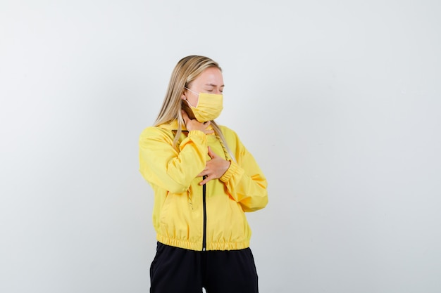Blonde lady in tracksuit, mask suffering from sore throat and looking sick , front view.
