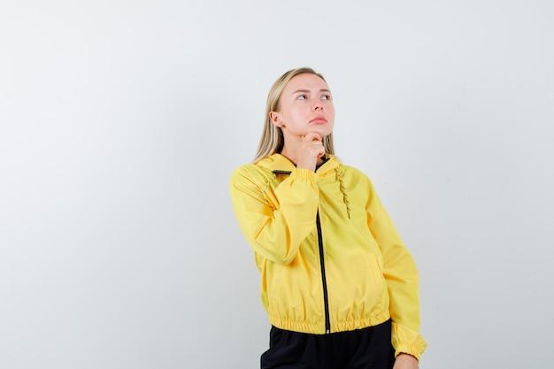 Signora bionda in tuta da ginnastica appoggiando il mento a portata di mano e guardando pensieroso, vista frontale.