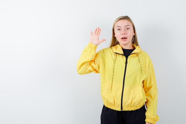 Signora bionda agitando la mano per il saluto in tuta da ginnastica e guardando stupito, vista frontale.