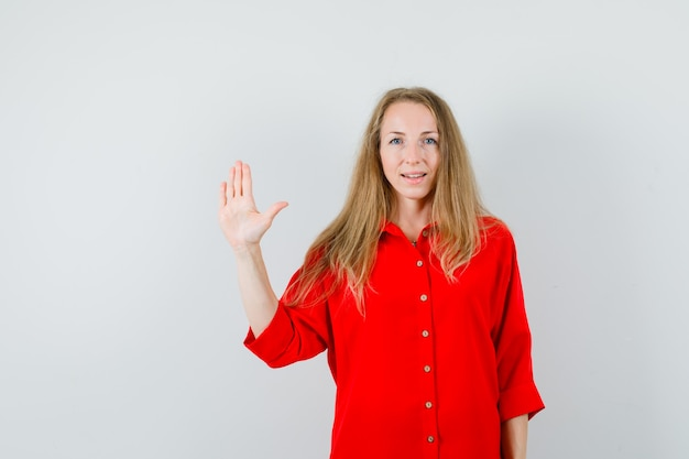 Blonde lady waving hand to say goodbye in red shirt and looking confident.