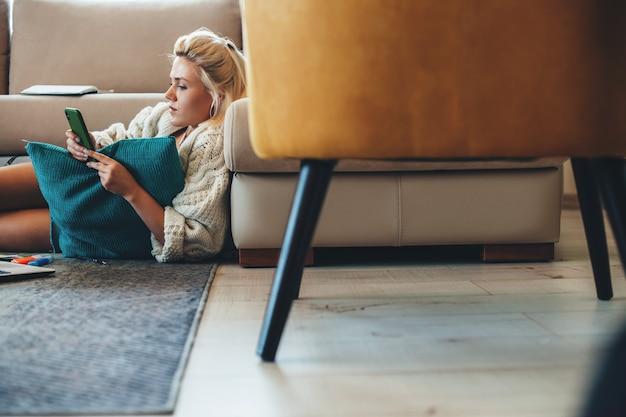 Блондинка в вязаном свитере использует телефон на полу во время работы за ноутбуком