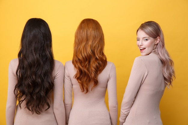 Blonde lady winking to back near brunette and redhead women.