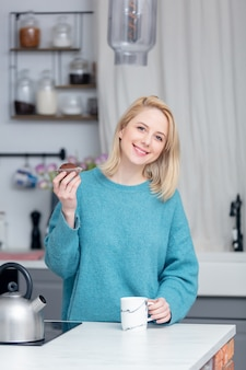 Blonde lady with cup of coffee at kitchen