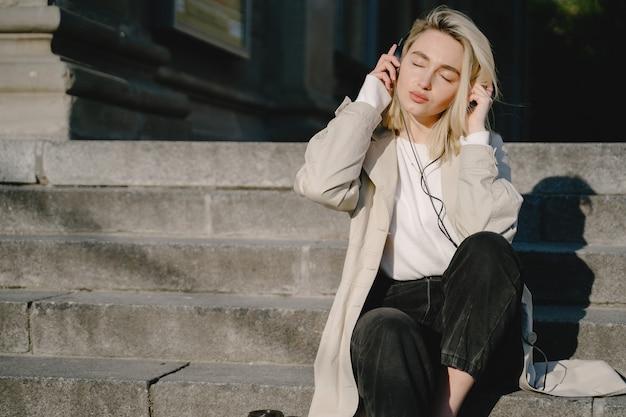 Bionda ascolta musica in una città estiva