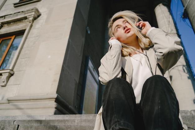 Blonde listen music in a summer city