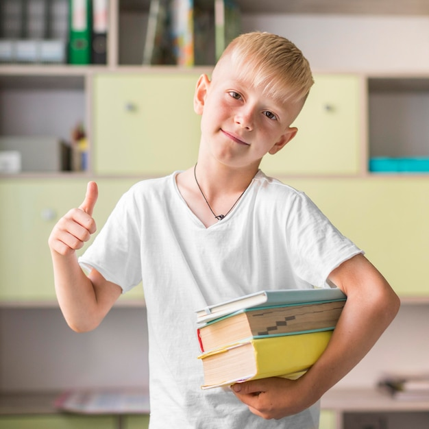 Blonde little boy holding a bunch of books