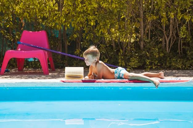 Blonde little boy in swimwear lying poolside