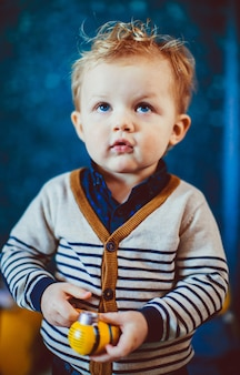 Blonde little boy with blue eyes stands in blue room
