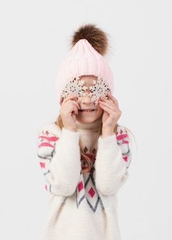 Blonde little girl covering her face wit snowflakes