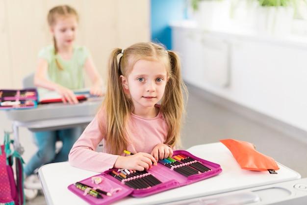 彼女の机の上の鉛筆ケースを持つ金髪の少女