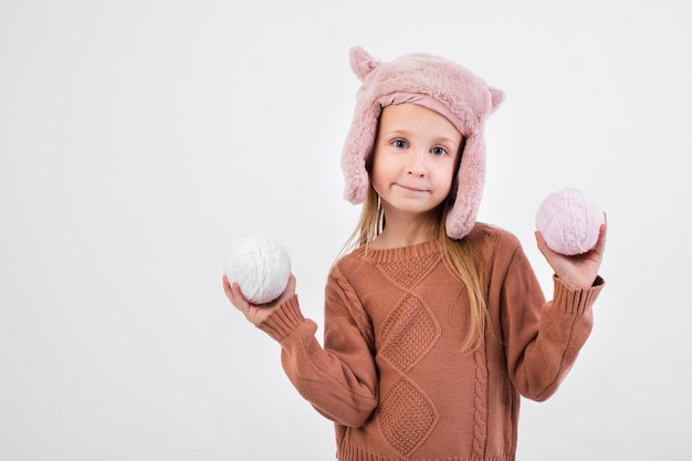Blonde little girl holding balls of wool