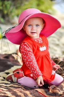 春に赤いドレスを着てビーチで帽子をかぶった金髪の少女