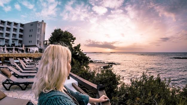 海と夕方の空を背景に見ている金髪の少女