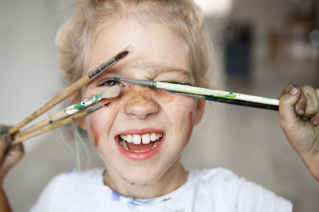 Blonde little girl in playful mood with paint on her freckled face and blue eyes covering her face with brushes