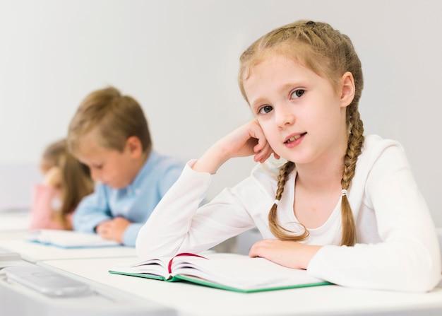 Bambina bionda seduta alla sua scrivania