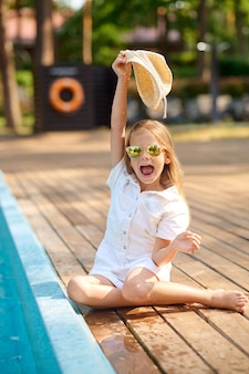 A blonde little girl sitting near the swimming pool