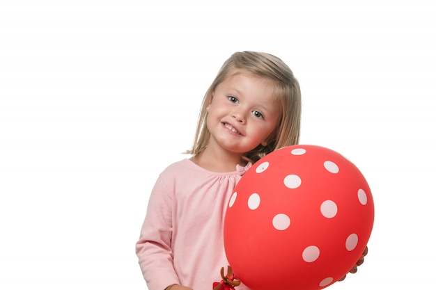 Blonde little girl smiling to camera with a balloon on white background