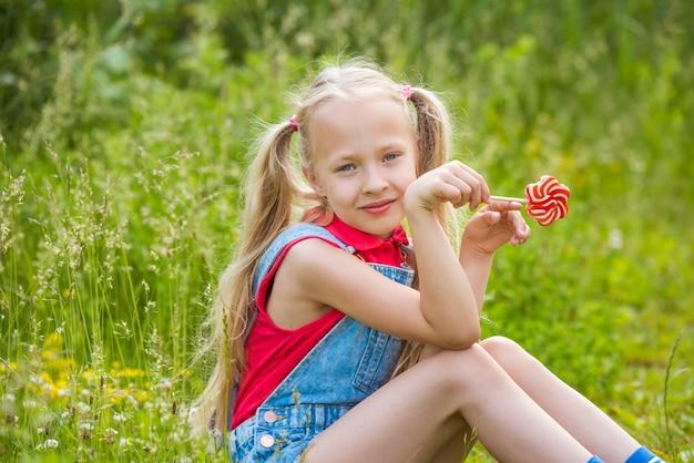Блондинка маленькая девочка с длинными волосами и конфетой на палочке
