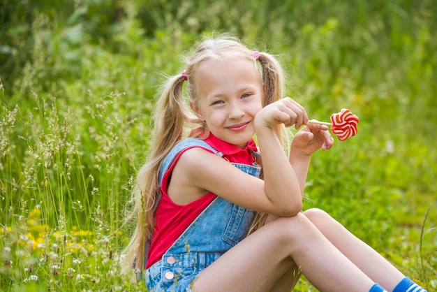 Blonde little girl with long hair and candy on a stick