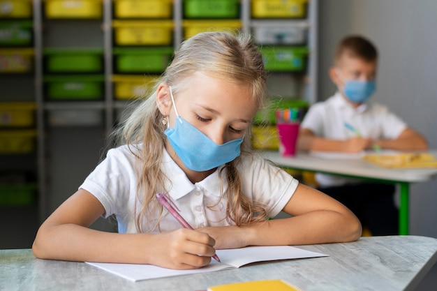 Blonde little girl writing while wearing a medical mask