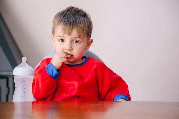 집에서 혼자서 먹는 금발 작은 아이