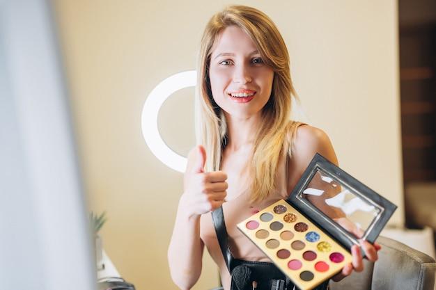 Светловолосый визажист демонстрирует подобие палитры теней, губной помады или косметики. визажист рекомендует.