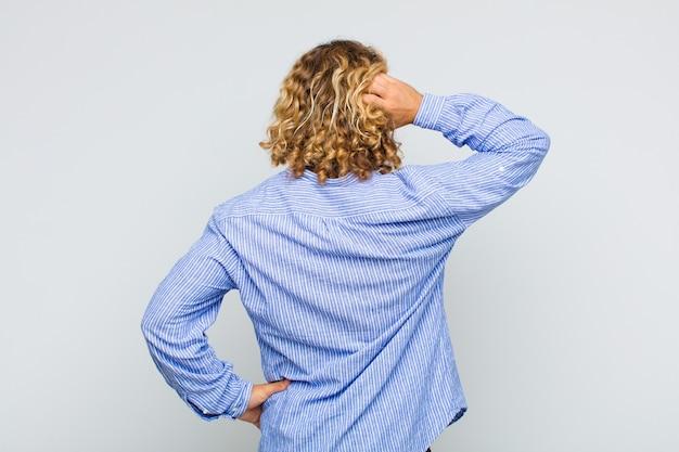 無知で混乱している金髪の男、解決策を考えて、腰に手を、頭に他の人、背面図