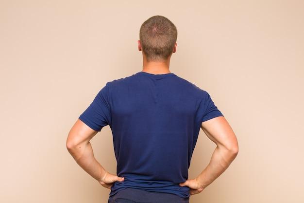 ブロンドの男性は、混乱したり、満腹になったり、疑問や質問を感じたり、疑問に思ったり、腰に手を当てたり、背面図を表示したりします