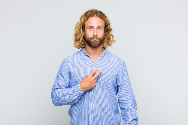 Светловолосый мужчина чувствует себя счастливым, позитивным и успешным, с рукой делает v-образную форму над грудью, показывая победу или мир