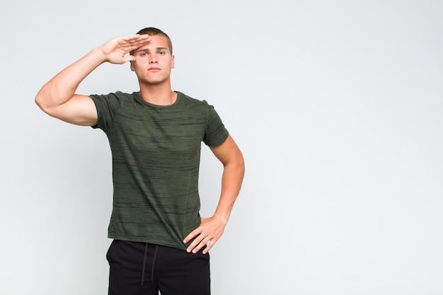 Блондин приветствует камеру военным салютом в знак чести и патриотизма, проявляя уважение