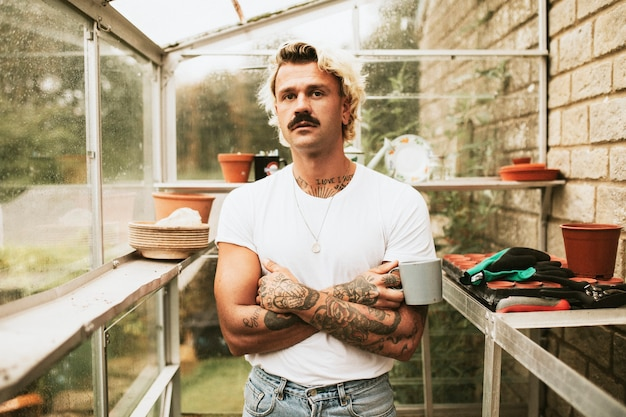 Blonde man his his greenhouse