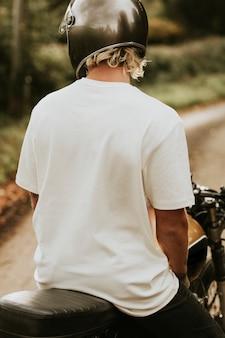 디자인 공간이 있는 자전거에 앉아 있는 흰색 티셔츠를 입은 금발의 남자