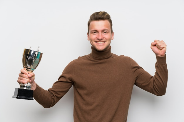 Blonde man over isolated white wall holding a trophy