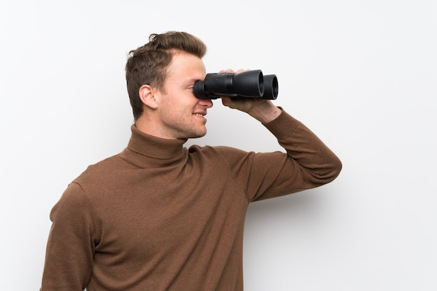 Blonde man over isolated white wall and looking in the distance with binoculars