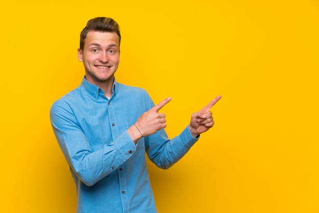 Blonde man over isolated yellow wall frightened and pointing to the side