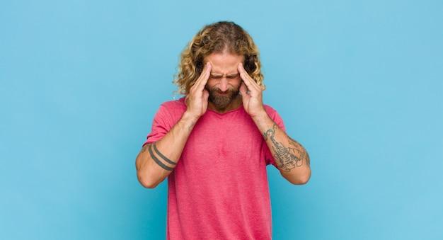 스트레스를 받고 좌절감을 느끼는 금발의 남자가 두통으로 압력을 받고 문제로 고민하고 있습니다.