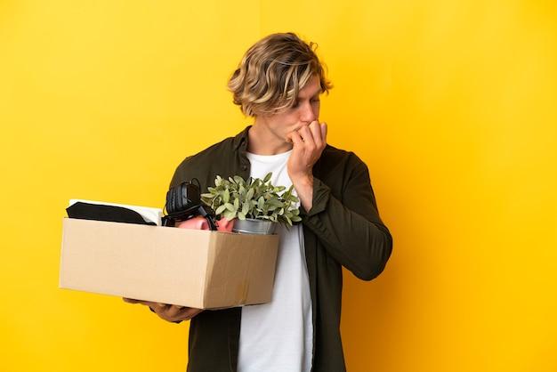 Блондинка делает ход, поднимая коробку, полную вещей, изолированную на желтом фоне, сомневаясь