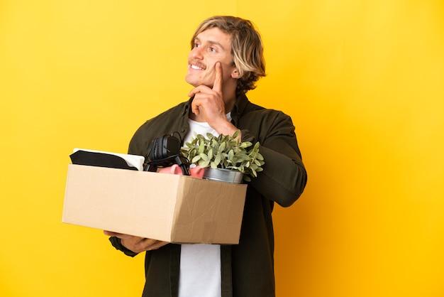찾고있는 동안 아이디어를 생각하는 노란색 배경에 고립 된 것의 전체 상자를 집어 들고 이동하는 금발의 남자