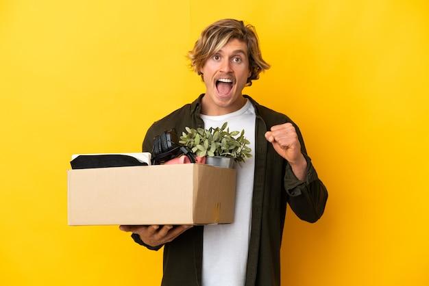 Светловолосый мужчина делает движение, поднимая коробку, полную вещей, изолированную на желтом, празднует победу в позиции победителя