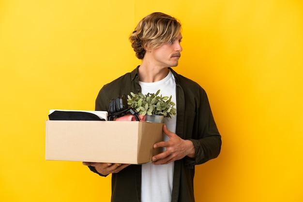 측면을 찾고 노란색에 고립 된 것들로 가득한 상자를 집어 들고 이동하는 금발의 남자