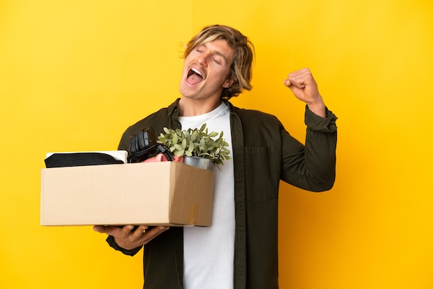 Блондинка делает движение, поднимая коробку, полную вещей, изолированную на желтой стене, празднует победу