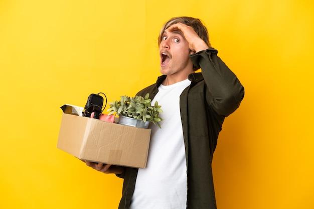 측면을 보면서 깜짝 제스처를 하 고 노란색 벽에 고립 된 것의 전체 상자를 집어 들고 이동하는 금발의 남자