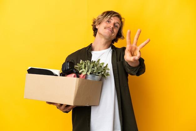 노란색 벽에 고립 된 것의 전체 상자를 집어 들고 손가락으로 세 세는 동안 움직임을 만드는 금발의 남자