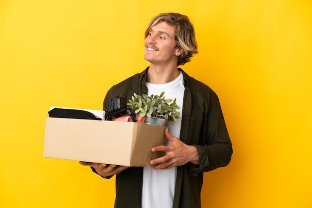 노란색 벽에 고립 된 것들로 가득 찬 상자를 집어 들고 웃고있는 동안 움직이는 금발의 남자