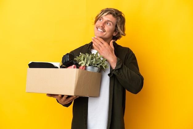 웃는 동안 찾고 노란색 벽에 고립 된 것의 전체 상자를 따기 동안 이동하는 금발의 남자