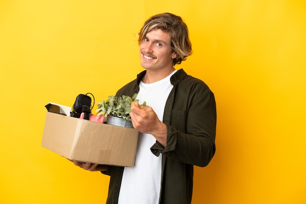 Блондинка делает движение, поднимая коробку, полную вещей, изолированную на желтой стене, делая денежный жест