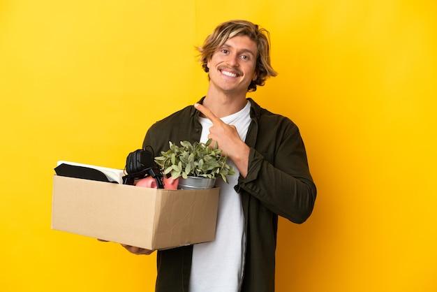 제품을 제시하기 위해 측면을 가리키는 노란색 벽에 고립 된 것들로 가득 찬 상자를 집어 들고 움직이는 금발의 남자