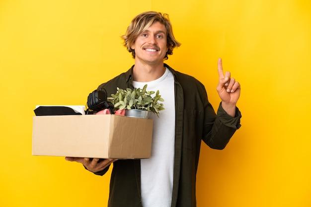 좋은 아이디어를 가리키는 노란색 벽에 고립 된 것들로 가득 찬 상자를 집어 드는 동안 이동하는 금발의 남자