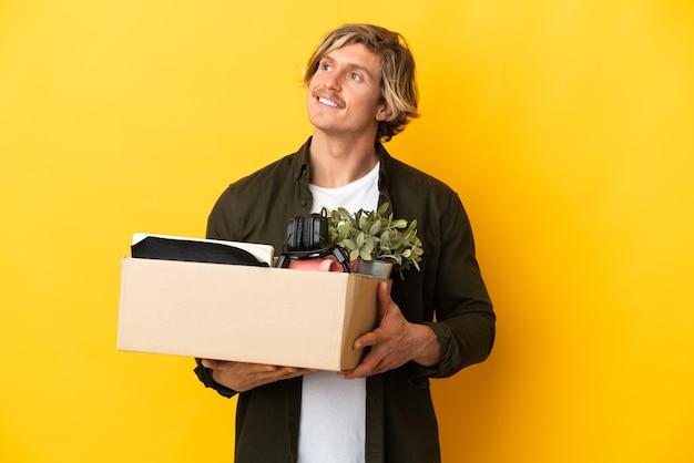 찾고있는 동안 아이디어를 생각하는 노란색 벽에 고립 된 것의 전체 상자를 집어 들고 이동하는 금발의 남자