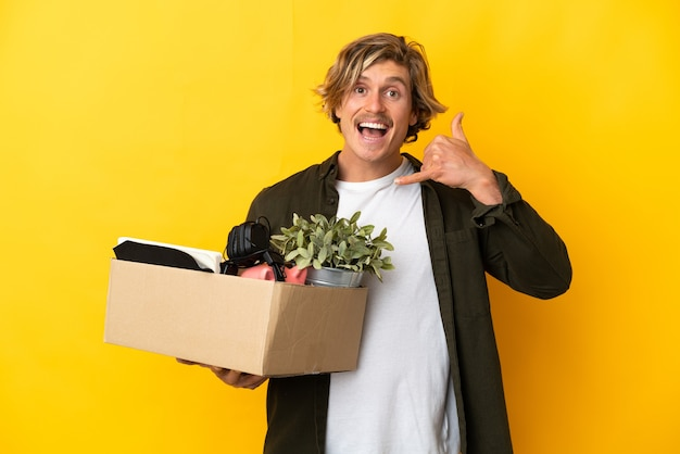 Blonde man making a move while picking up a box full of things isolated on yellow making phone gesture. call me back sign